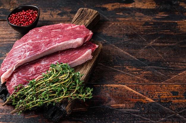 Surowy stek z polędwicy wołowej lub stek picanha na desce z tymiankiem. stół z ciemnego drewna. widok z góry.