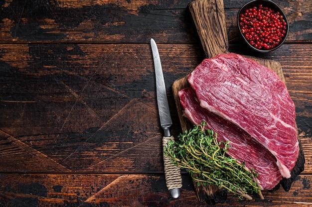 Surowy stek z polędwicy wołowej lub stek picanha na drewnianej desce z tymiankiem