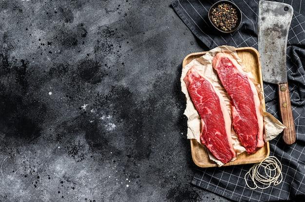 Surowy stek z polędwicy wołowej na drewnianej tacy. marmurkowe mięso wołowe. widok z góry