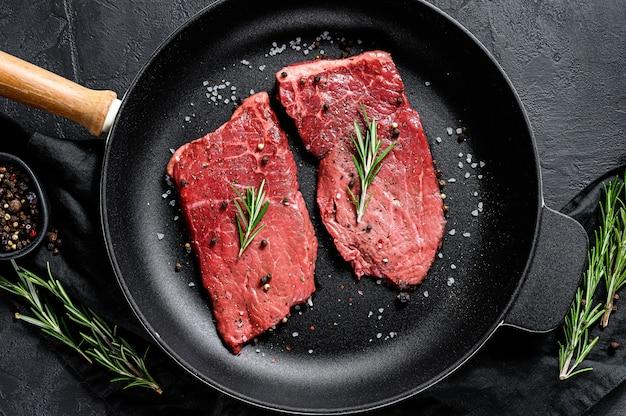 Surowy stek z polędwicy wołowej na patelni. mięso wołowe. widok z góry