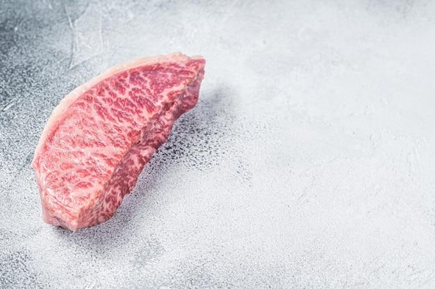 Surowy stek z polędwicy wołowej wagyu, mięso wołowe kobe. białe tło. widok z góry. skopiuj miejsce.