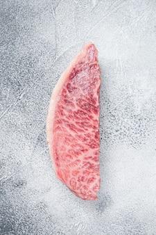 Surowy stek z polędwicy wołowej wagyu, mięso wołowe kobe. białe tło. widok z góry.