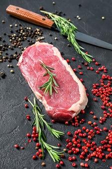 Surowy stek z rostbefu lub strips new york z ziołami.
