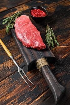 Surowy stek z rostbefu na desce do krojenia, marmurkowa wołowina.