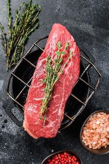 Surowy stek z rostbefu na grillu, marmurkowa wołowina.