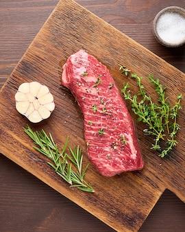 Surowy stek z rostbefu z solą rozmarynowo-tymiankową i ząbkiem czosnku na drewnianej desce do krojenia powyżej