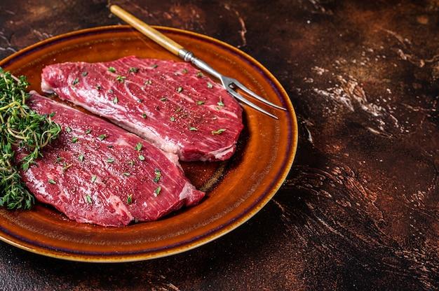 Surowy stek z rumsztyku lub polędwicy wołowej na rustykalnym talerzu z tymiankiem i oliwą z oliwek. widok z góry.