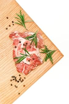Surowy stek z świeżego mięsa wołowego z przyprawami rozmarynu i pieprzu na desce do krojenia
