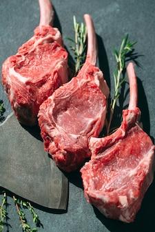 Surowy stek z tasakiem do mięsa na ciemnej kamiennej powierzchni.