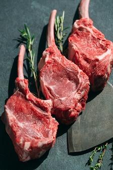 Surowy stek z tasakiem do mięsa na ciemnym kamieniu.
