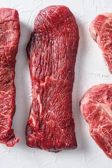 Surowy stek z tri-tip do cięcia ekologicznego mięsa z grilla pokroić widok z góry z bliska na biały betonowy stół w pionie.