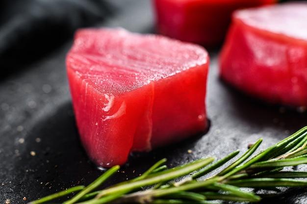 Surowy stek z tuńczyka. czarne tło. widok z góry. ścieśniać