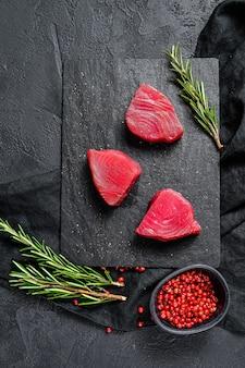 Surowy stek z tuńczyka. czarne tło. widok z góry