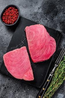 Surowy stek z tuńczyka na marmurowej desce do krojenia. czarne tło. widok z góry.