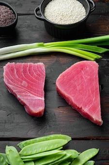 Surowy stek z tuńczyka, świeży czerwony filet z tuńczyka ze składnikami, zielonym groszkiem, sezamem i zestawem przypraw, na starym ciemnym drewnianym stole
