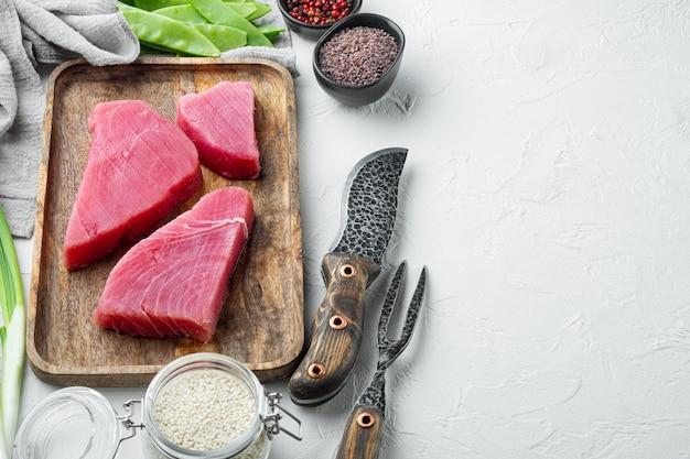 Surowy stek z tuńczyka, świeży filet z czerwonego tuńczyka ze składnikami, zielonym groszkiem, sezamem i przyprawami, na drewnianej tacy, na białym kamiennym tle, z copyspace i miejscem na tekst