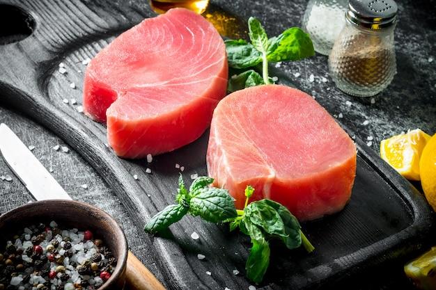 Surowy stek z tuńczyka z ziołami i przyprawami na rustykalnym stole