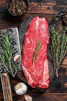 Surowy stek z wołowiny na desce do krojenia z tasakiem. ciemne drewniane tło. widok z góry.