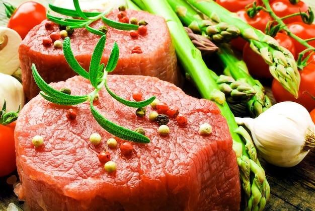 Surowy stek z zielonymi szparagami na desce