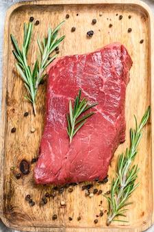 Surowy stek zad na drewnianej tacy. mięso wołowe. widok z góry.