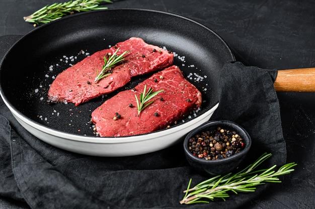 Surowy stek zad na patelni. mięso wołowe. widok z góry