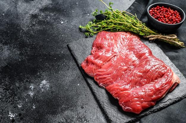 Surowy stek ze spódnicy, marmurkowe mięso. czarne tło. widok z góry. skopiuj miejsce.