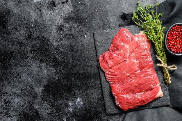 Surowy stek ze spódnicy, marmurkowe mięso. widok z góry. skopiuj miejsce