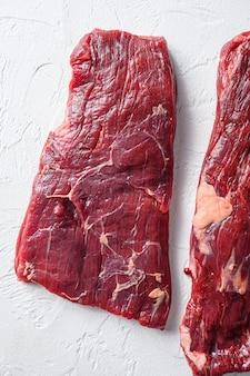 Surowy stek ze spódnicy, stek z flanki, do cięcia mięsa organicznego z grilla, widok z góry z bliska