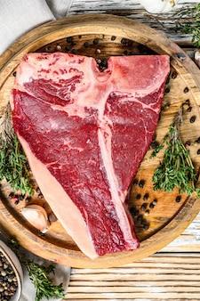 Surowy stek ze świeżego mięsa z przyprawami, czosnkiem i rozmarynem. ekologiczna wołowina z kością. białe tło. widok z góry.