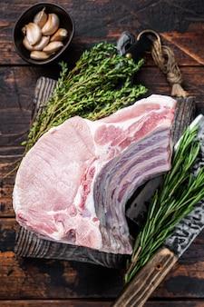 Surowy stojak na kotlety schabowe z żeberkami na desce rzeźnika z tasakiem do mięsa.