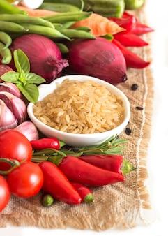 Surowy suchy cały upolished ryż w pucharze z warzywami na burlap odizolowywa na bielu zakończeniu up