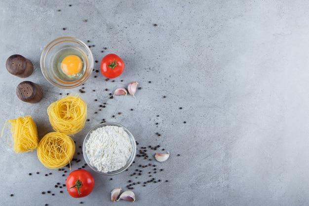 Surowy suchy makaron gniazdo z surowym jajkiem i warzywami na kamiennym tle.