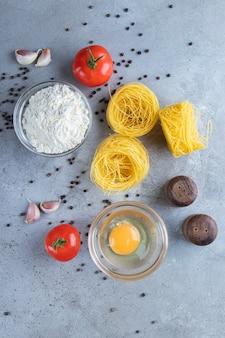Surowy suchy makaron gniazdowy z surowym jajkiem i warzywami na kamiennej powierzchni.