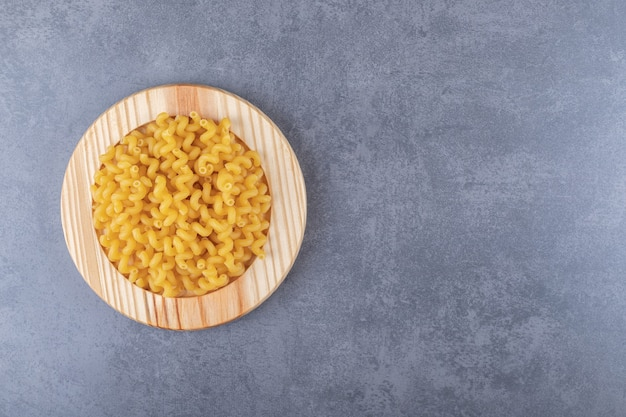Surowy suchy makaron na drewnianym talerzu.