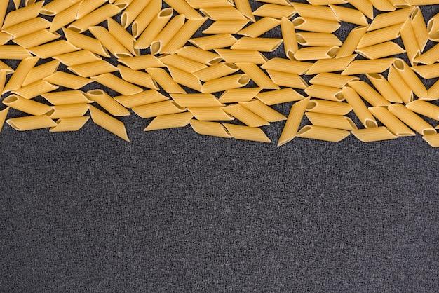 Surowy suchy włoski makaron na szarym tle