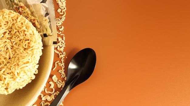 Surowy, suszony makaron instant w głębokim talerzu z przyprawami i jednorazową plastikową czarną łyżką. skopiuj makaron kosmiczny, do przygotowania którego wystarczy zalać wrzącą wodą.