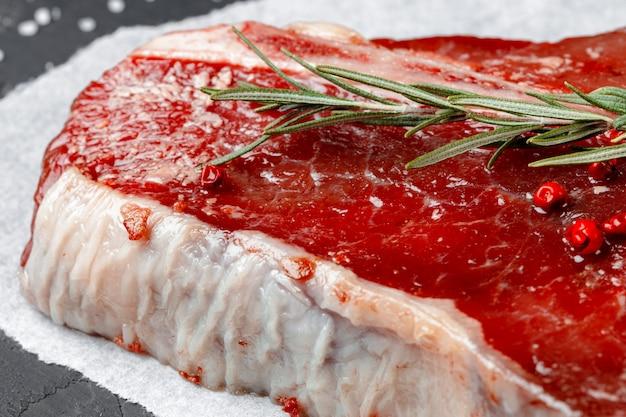 Surowy świeżego mięsa kości stek z pikantność na ciemnym tle, zamyka up