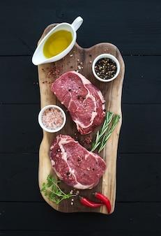 Surowy świeżego mięsa ribeye stku antrykot i przyprawy na tnącej desce nad ciemnym drewnianym tłem.