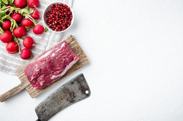 Surowy świeży antrykot marmurkowy z zestawu mięsnego black angus prime, pokrojona w polędwicę filet mignon, ze starym nożem rzeźniczym, na białym kamieniu