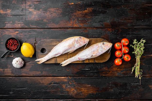 Surowy świeży cefal lub barabulka cały zestaw ryb, ze składnikami i ziołami, na starym ciemnym tle drewnianego stołu, widok z góry płasko leżał, z miejscem na tekst