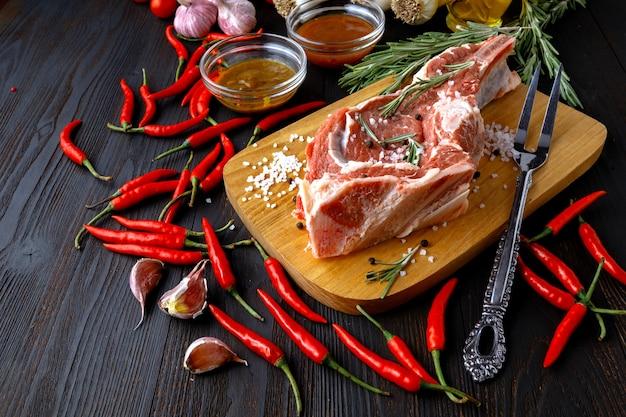 Surowy świeży mięso z składnikami dla gotować na zmroku stole