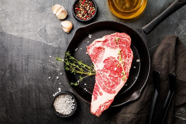 Surowy świeży stek ribeye, mięso wołowe z przyprawami i patelnią do gotowania na ciemno