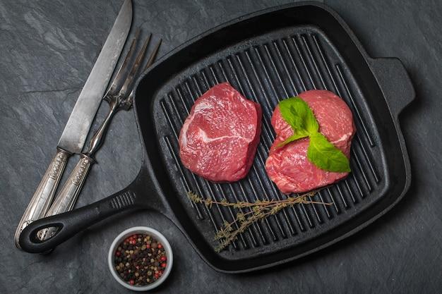 Surowy świeży stek wołowy na patelni grillowej