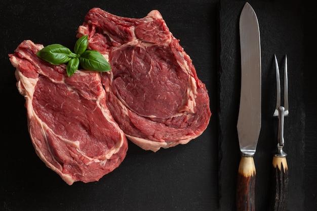 Surowy świeży stek wołowy z kością, przyprawami i przyprawami na kamiennej desce do krojenia.