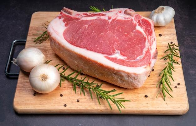 Surowy świeży stek wołowy żeberka z ziołami na drewnianym tle zbliżenie widok marmuru stek żeberkowy