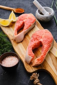 Surowy świeży stek z łososia na drewnianej desce do krojenia