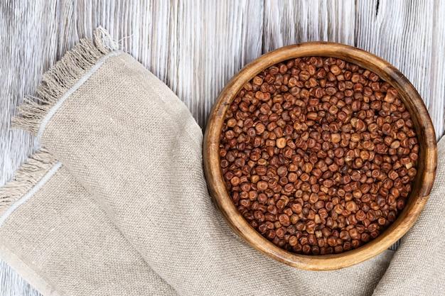 Surowy szary groszek w okrągłej drewnianej misce na jasnym drewnie żywność ekologiczna zdrowej diety