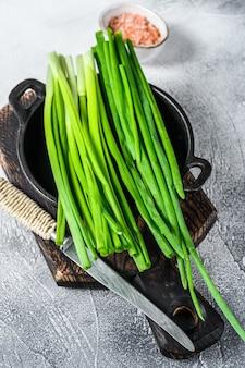 Surowy szczypiorek zielonej cebuli. białe tło. widok z góry.