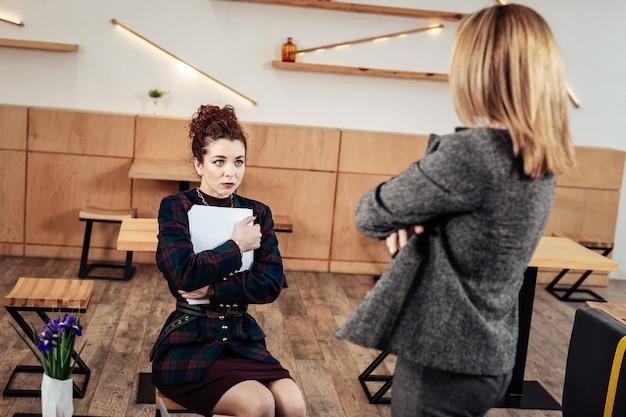 Surowy szef. młoda praktykantka nosząca stylowy kostium czuje się zaniepokojona słuchaniem swojej surowej szefowej
