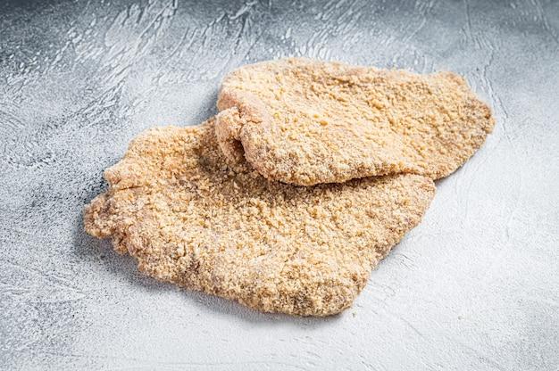 Surowy sznycel z kurczaka eskalopki w bułce tartej. białe tło. widok z góry.
